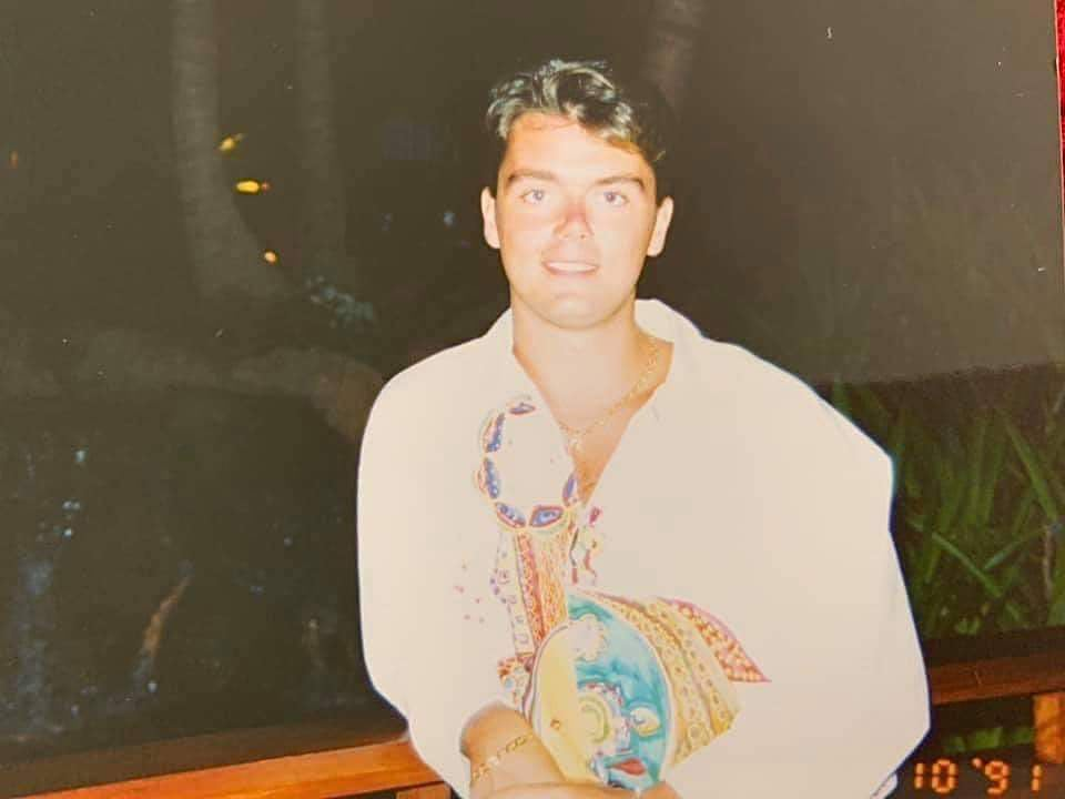 Simon Stanley in 1991, leaning casually against a cruise ship rail, wearing a loud tropical print shirt.