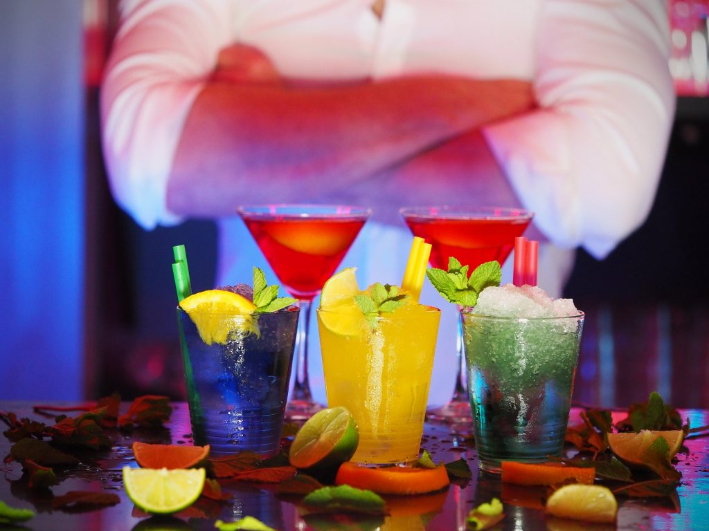 Stock photo of five vividly coloured cocktails with crushed ice and multicoloured straws, with male barman behind with folded arms.