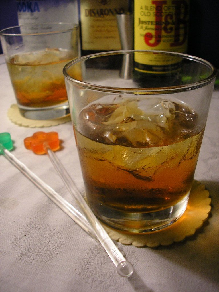 Two glass tumblers with Rusty nail cocktail and two stirrers alongside.