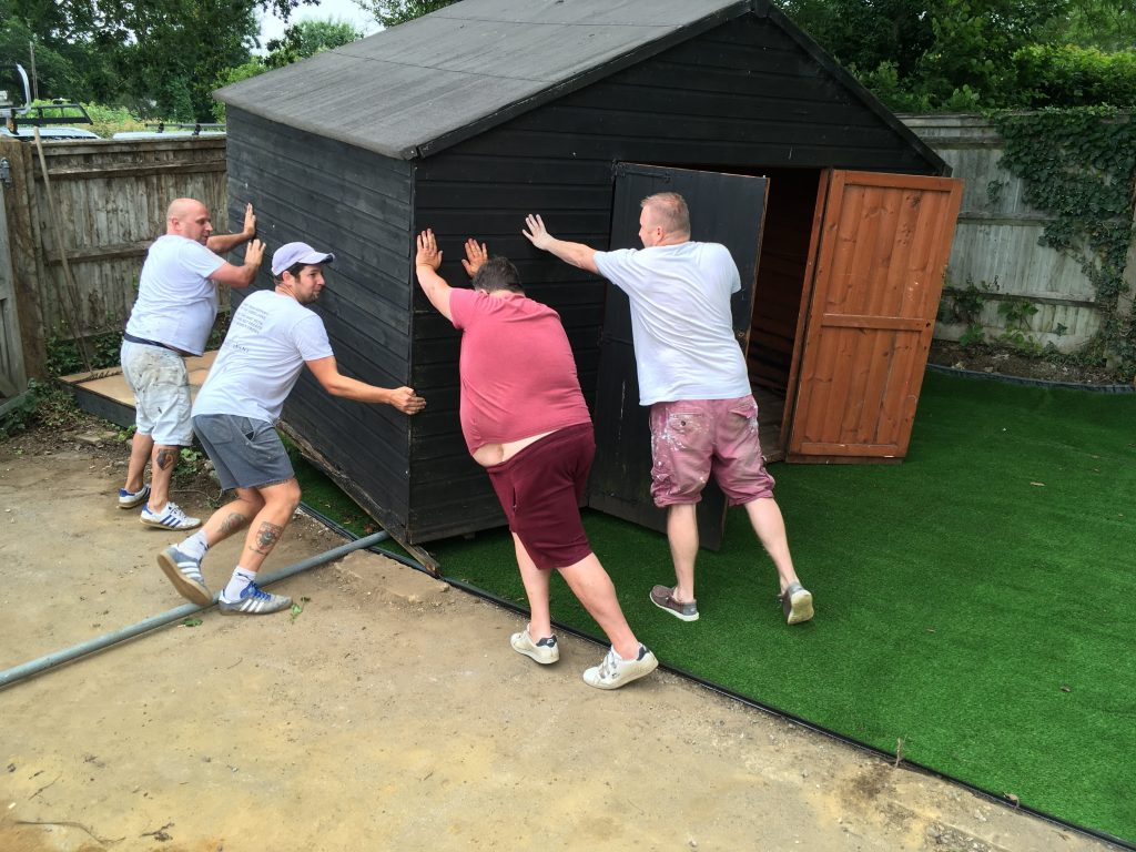 Volunteers shove a shed into place as part of the development