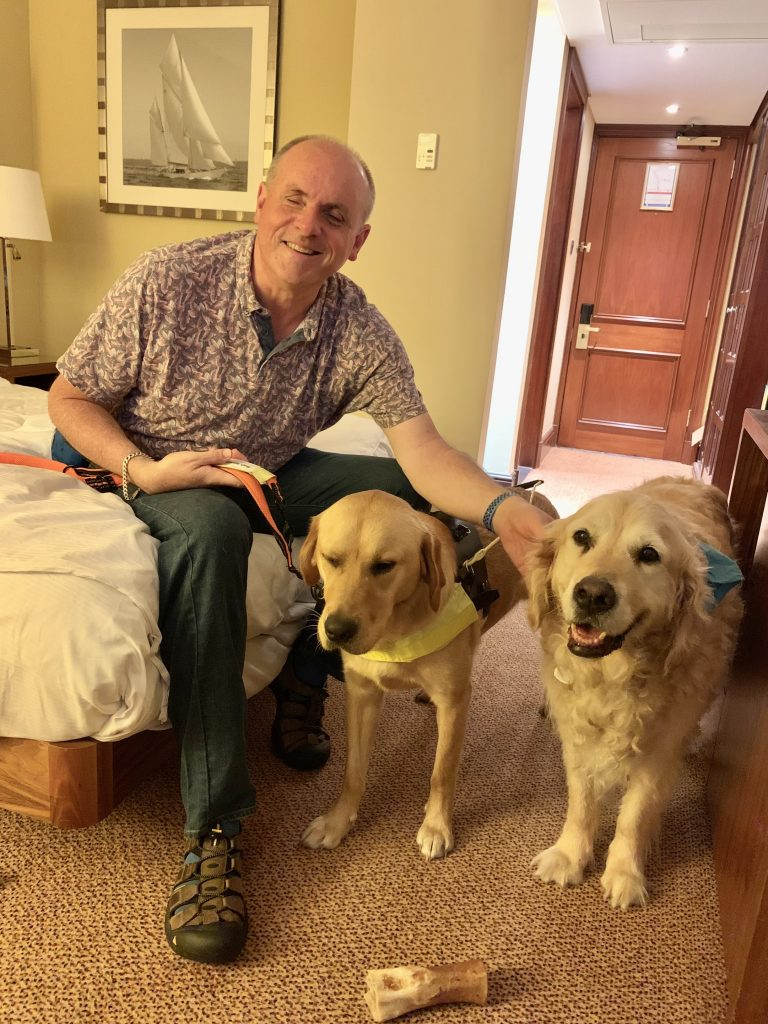 John Welsman sitting on bed with Benjy and Breck, retired guide dog