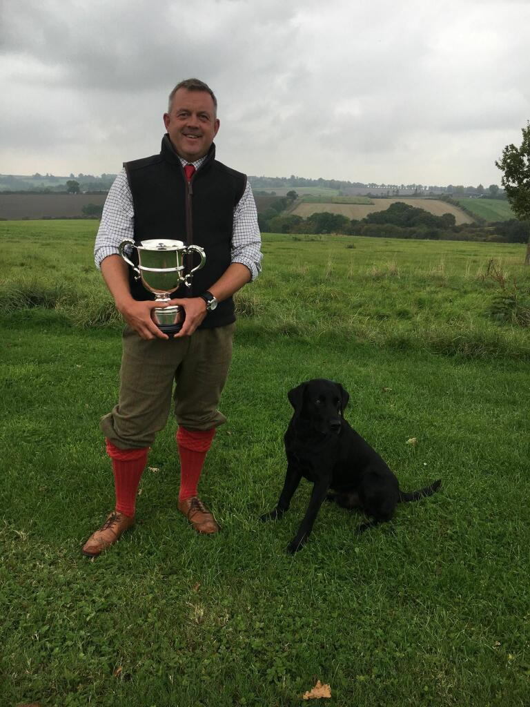 Jason Mayhew smiling broadly in a field, holding the Field Champion cup, won by Drake the black labrador gun dog who sits next to him.