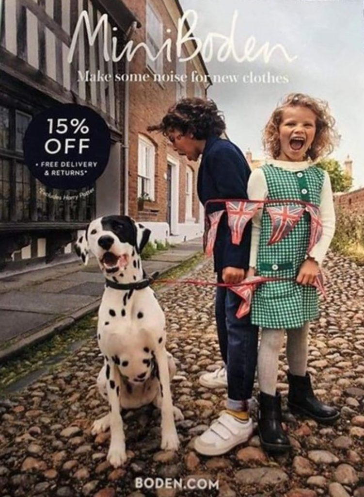 Front cover of Mini Boden clothes catalogue, featuring Alfie the model Dalmatian with goofy look and two child models with union jack bunting tied around them and onto Alfie's collar.